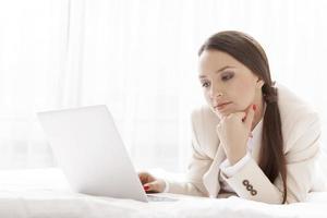 jovem empresária usando laptop no quarto de hotel