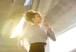 jovem mulher correndo no ambiente urbano foto