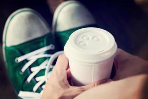 jovem mulher tomando café do copo descartável foto