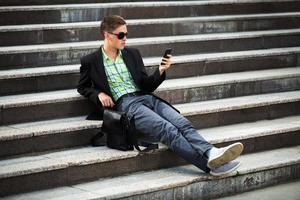 jovem com um telefone móvel, sentado nos degraus foto