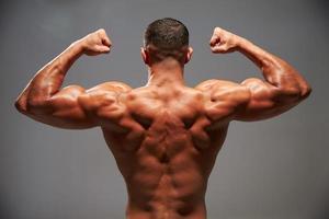 fisiculturista masculina flexionando os bíceps, vista traseira foto