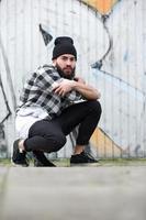 homem urbano sentado por grafite foto
