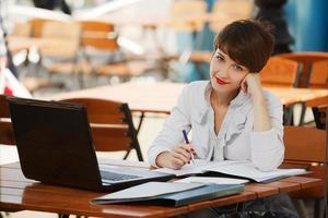 jovem empresária com laptop em um café na calçada foto