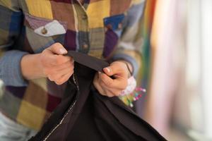 closeup na costureira trabalhando com tecido foto
