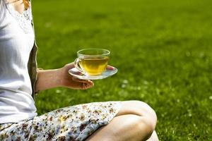 jovem mulher bebendo chá no parque foto