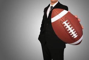 empresário com bola de futebol americano foto