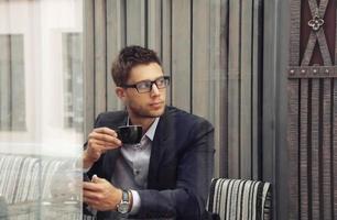 empresário atraente, bebendo café expresso na cidade foto