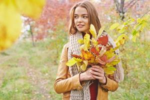menina com um monte de folhas foto