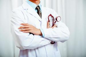 médico, dobrar braços, segurando, estetoscópio foto