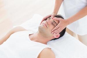homem recebendo massagem na cabeça foto