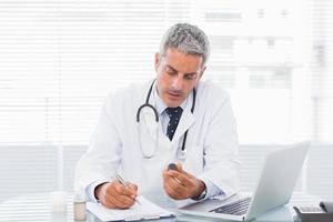 médico segurando a medicação e escrever uma receita foto