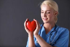 médico com estetoscópio segurando coração, isolada no fundo cinza foto