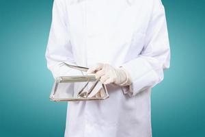 mão do dentista ou assistentes dentários. segure ferramentas de dentistas. foto