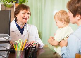 médico sorridente, conversando com a mãe do bebê foto