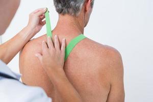 médico examinando o ombro do paciente foto
