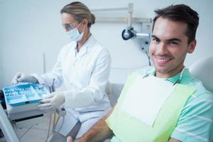 homem sorridente, à espera de exame dentário foto