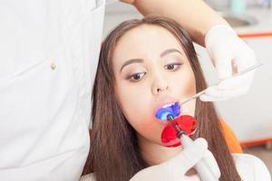 médico dentista trata os dentes menina paciente no consultório odontológico foto