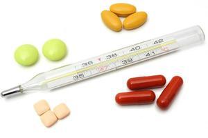 conceito de doença com termômetro e comprimidos foto