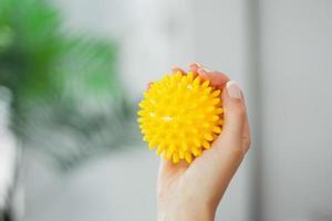 close-up de mão feminina segurando bola de massagem foto