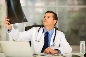 médico olhando o raio x do paciente no escritório foto