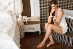 teste de gravidez. mulher preocupada, olhando para um teste foto
