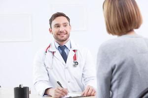 cardiologista sorridente, conversando com o paciente foto