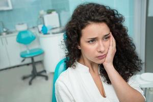 jovem mulher que sofre de dor de dente foto