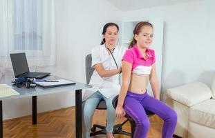 menina na visita de um médico foto