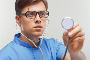 médico com um estetoscópio nas mãos foto