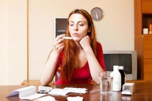 mulher triste medir temperatura com termômetro em casa foto
