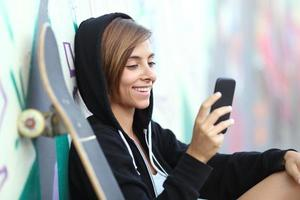 jovem patinadora adolescente feliz, usando um telefone inteligente foto