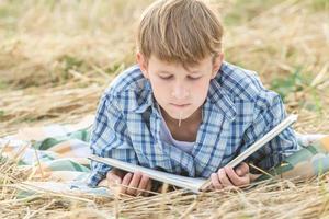 adolescente deitado com livro foto