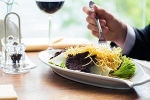 mãos masculinas comendo salada foto
