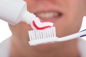 macho com escova de dentes e creme dental