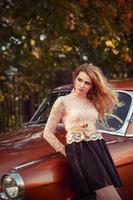mulher elegante, de pé com um carro retrô em vestido de moda foto