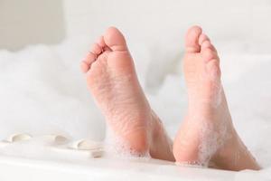 closeup de pés na borda da banheira