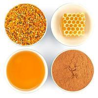 mel, favo de mel, pólen e canela em tigelas foto