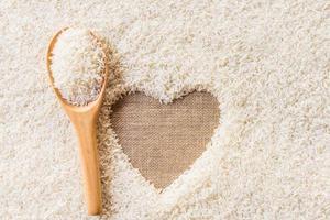 colher de pau no espaço de fundo de arroz no coração do meio foto