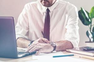 empresário, escrevendo notas e usando o laptop na mesa de escritório foto