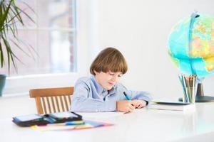 adorável menino rindo fazendo sua lição de casa na mesa branca foto
