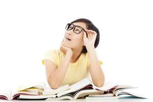 menina asiática jovem estudante pensando com livro foto