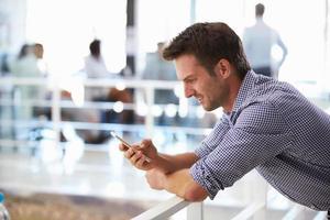 retrato de homem no escritório usando telefone inteligente foto