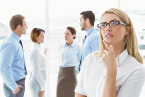 empresária pensativa com colegas por trás
