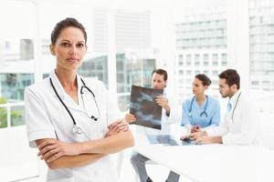 médico com colegas examinando raios-x no consultório médico foto