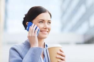 mulher sorridente com café chamando em smartphone foto