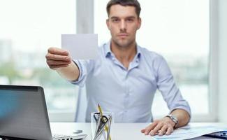 empresário, mostrando o cartão de papel em branco no escritório foto