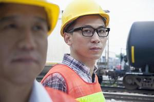 engenheiro sério fora na frente da linha férrea foto