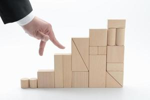 mão da pessoa de negócios e escadas de bloco de madeira foto