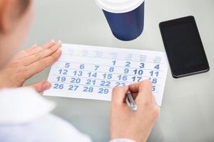 empresário com caneta escrevendo no calendário e celular foto