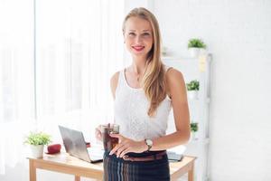 retrato de mulher de negócios bem sucedido bonito segurando xícara café olhando foto